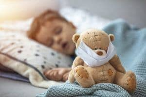 Little boy sleeping in bed with medical mask embracing his teddy bear. Home isolation coronavirus covid-2019 quarantine.