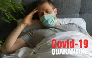 Sick man with medical mask lying in bed during Corona virus quarantine.